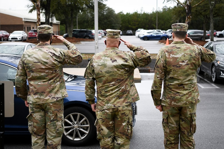 Photo of three Airmen saluting a vehicle