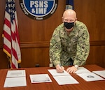 Capt. Jip Mosman, commander, Puget Sound Naval Shipyard & Intermediate Maintenance Facility, signs the application to become a Star Site under the Occupational Safety & Health Administration's Voluntary Protection Program, Feb. 18, 2021, at PSNS & IMF, in Bremerton, Wash.
