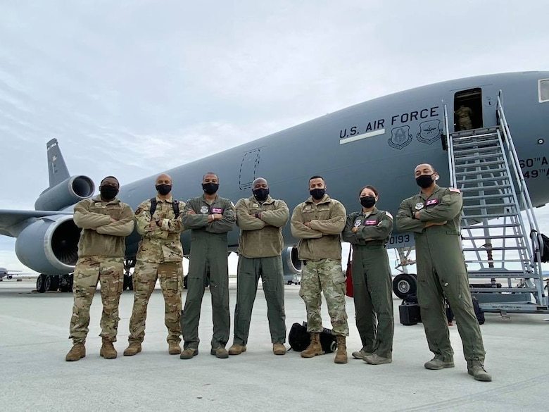 Military members in flight suits stand shoulder to shoulder in front of a KC-10 Extender aircraft