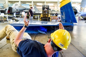 U.S. Air Force Master Sgt. Brandon Baimbridge, 735th Air Mobility Squadron superintendent, directs a forklift carrying the wing of a U.S. Navy Blue Angel F/A-18 on Joint Base Pearl Harbor-Hickam, Hawaii, Feb. 9, 2021.  The Pearl Harbor Aviation Museum's mission is to steward America's first aviation battlefield of World War II – sharing the artifacts, personal stories, the impact and response to the attack on December 7, 1941, and the Pacific region battles that followed. (U.S. Air Force photo by Tech. Sgt. Anthony Nelson Jr.)
