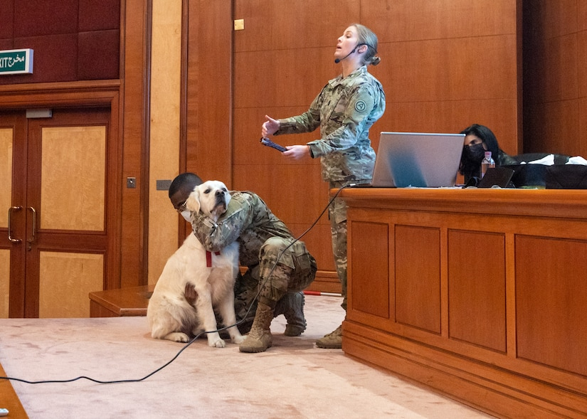 Cpt. Emrick Whitfield, veterinary clinic officer in charge, Area Support Group Kuwait, and Sgt. Iisa Stephens, veterinary clinic noncommissioned officer in charge, ASG Kuwait, demonstrate proper calm and restraint techniques for canines during a canine behavior and safety seminar at the Public Authority of Agriculture Affairs and Fish Resources in Rabia, Kuwait, Feb. 2, 2021. The use of proper restraining techniques protects both the person and animal, while also calming the dog.