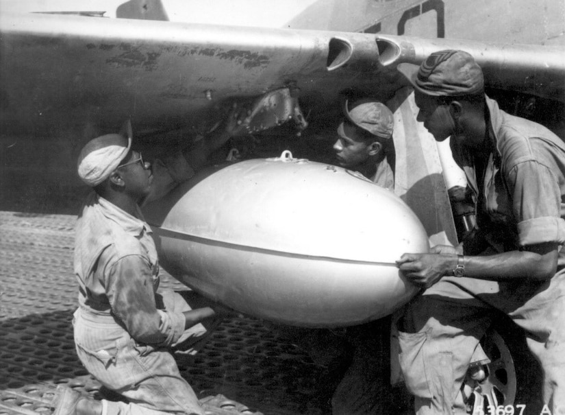 Editor's note: photo and caption were pulled from the National Archives Catalog. Members of the ground crew of a Negro fighter squadron of the 15th U.S. Air Force in Italy place a loaded wing tank on a P-51 Mustang before the group takes off on another mission escorting bombers over enemy targets. The squadron uses auxiliary fuel tanks for long-distance flights. Left to right: T/Sgt. Charles K. Haynes, S/Sgt. James A. Sheppard, and M/Sgt. Frank Bradley. N.d. 208-AA-49E-1-3.