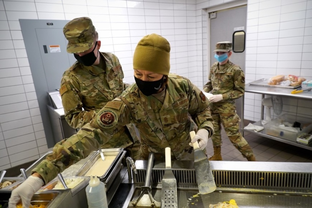 Chief Master Sgt. of the Air Force JoAnne S. Bass prepares to assemble an omelet with Airman 1st Class Samuel Hood, 319th Force Support Squadron food service apprentice, left, in the dining facility on Grand Forks Air Force Base, N.D., Feb. 12, 2021. During her visit, Bass met with a variety of Airmen and discussed her priorities, Air Force administrative changes, and addressed questions on a range of topics.