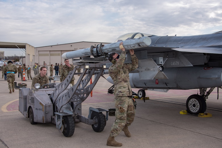 (Right) Tech. Sgt. Dalton King, 301st Fighter Wing Aircraft Maintenance Squadron load crew lead, lifts an AIM-120 missile, preparing to secure it to the 301st Fighter Wing's F-16, as (left) Senior Airman Jaymes Fincher positions the weapons loader during a weapons load competition at U.S. Naval Air Station Joint Reserve Base Fort Worth, Texas on February 5, 2021. The competition consists of four, three-person AMXS load crews quickly uploading weapons on 301st Fighter Wing F-16s, while maintaining a strict attention to detail, with hopes of winning load crew of the year. (U.S. Air Force photo by Senior Airman William Downs)