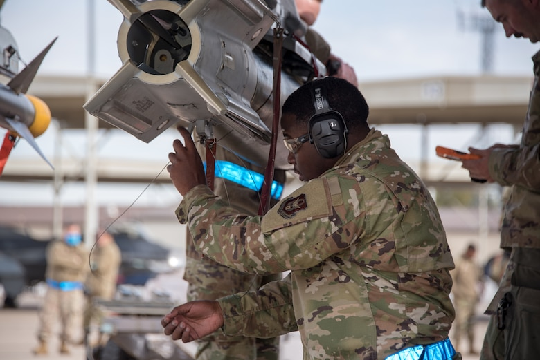 Senior Airman Keyshawn Johnson, 301st Fighter Wing Aircraft Maintenance Squadron weapons load crew member, routes the arming lanyard to the F-16 wing release lever of the GBU-12 bomb during a weaponsload competition at U.S. Naval Air Station Joint Reserve Base Fort Worth, Texas on February 5, 2021. Loading aircraft munitions is how the weapons section fit into the 301 FW mission—to train, deploy, combat ready Airmen. (U.S. Air Force photo by Senior Airman William Downs)