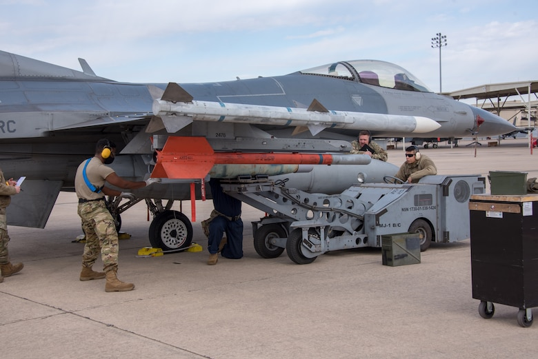 (Left) Tech. Sgt. Shawn Wood, 301st Fighter Wing Aircraft Maintenance Squadron load crew lead, (center) Senior Airman Brandon Knuckles and (right) Senior Airman Emanuel Aguilar load a GBU-12 bomb to the 301st Fighter Wing's F-16, while being evaluated by (center right) Tech. Sgt. Dakota Daniel during a weapons load competition at U.S. Naval Air Station Joint Reserve Base Fort Worth, Texas on February 5, 2021. The weapons load competition occurs annually, giving the weapons sections a chance to put their four weapons load crews head-to-head loading munitions, testing their knowledge and conducting a uniform inspection to see who the best is. (U.S. Air Force photo by Senior Airman William Downs)