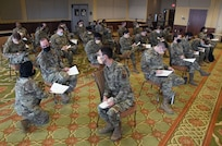 Members of the 81st Medical Group completes inprocessing paper work for deploying inside the Bay Breeze Event Center at Keesler Air Force Base, Mississippi, Feb. 16, 2021. More than 150 Dragon Medics were preparing to deploy to support our nation's COVID-19 vaccine inoculations requirements. (U.S. Air Force photo by Kemberly Groue)