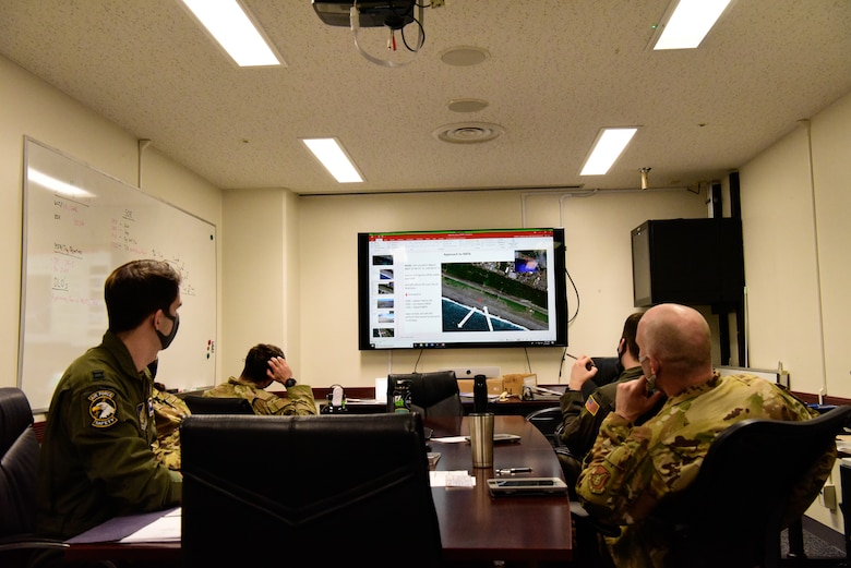 Airmen sit in a conference room observing a powerpoint slide