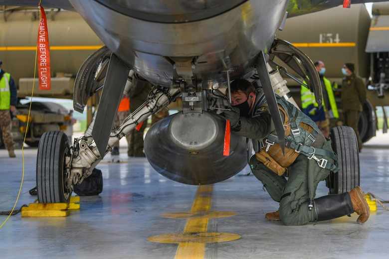U.S. Air Force 1st Lt. Kyle Senn, 555th Fighter Squadron pilot, pins a warning tag onto an F-16 Fighting Falcon during an Agile Combat Employment exercise at Amendola Air Base, Italy, Feb. 16, 2021. ACE exercises are designed to ensure U.S. Air Forces in Europe, along with allies and partners, are ready for potential short or no-notice contingencies. (U.S. Air Force photo by Senior Airman Ericka A. Woolever)