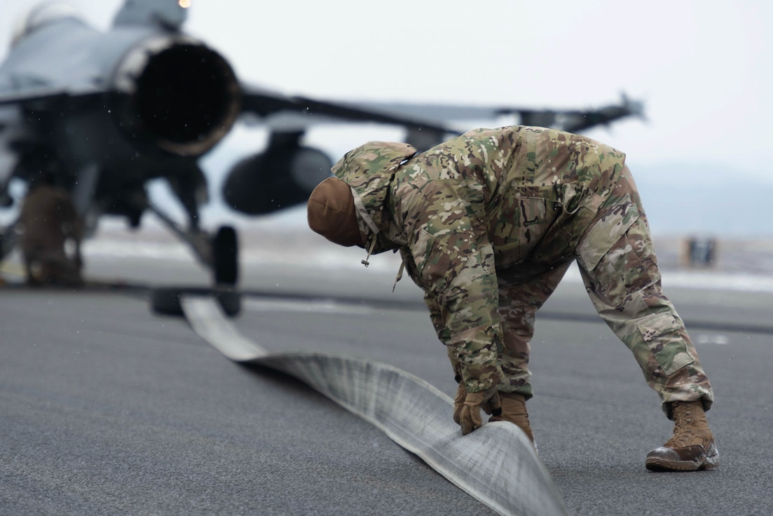 An Airman inspecting a barrier arresting kit during training.