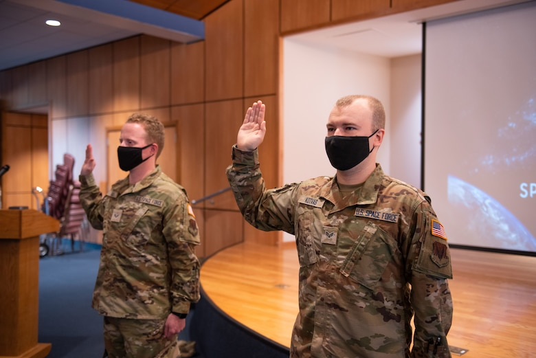 Two uniformed members stand to take an oath