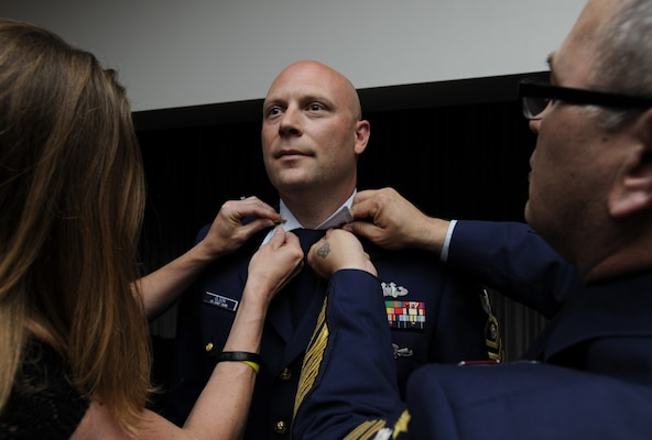 Cyndy Olson and Master Chief Petty Officer of the Coast Guard Steven Cantrell affix new collar devices to Ryan Olson's uniform during the 2014 Coast Guard Enlisted Persons of the Year Banquet at Joint Base Anacostia-Bolling in Washington, D.C., May 7, 2015. During the ceremony, Olson was recognized as the Enlisted Person of the Year - Reserve Component, an honor that comes with a meritorious advancement - in Olson's case, an advancement from petty officer first class to chief petty officer. (U.S. Coast Guard photo by Chief Petty Officer Kyle Niemi)