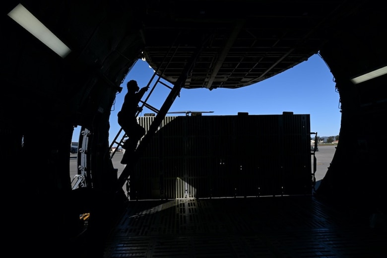 An Airman walks up the stairs into the second level of a C-5M Super Galaxy