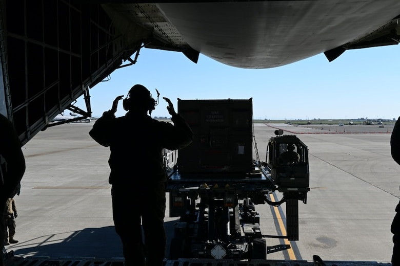 An Airman in a uniform and headset taxis in cargo into the gaping maw of a C-5M Super Galaxy