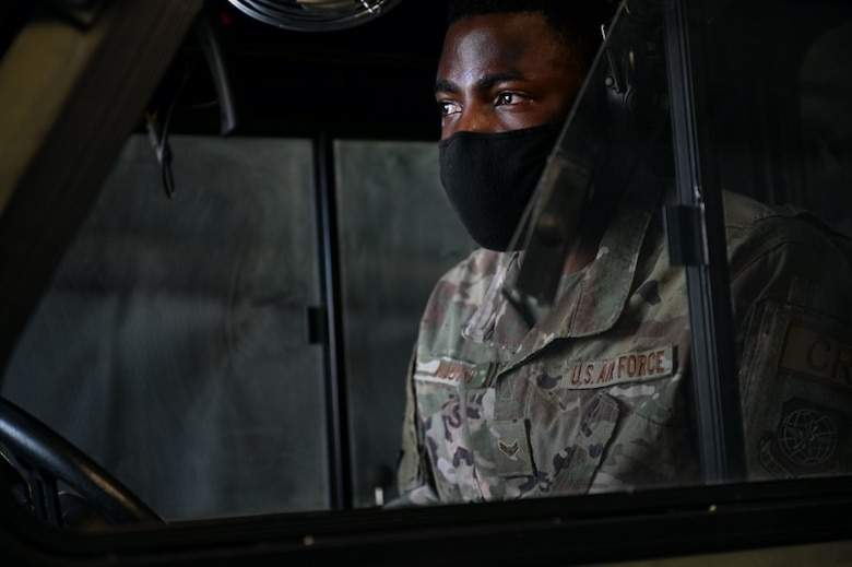 A military member in uniform and mask looks off screen
