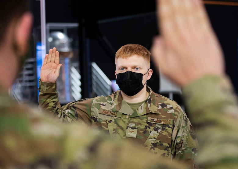 Airman 1st Class Noah Goethal, 88th Communications Squadron, takes the oath of enlistment on Feb. 11, becoming a Space Force specialist 3 during a ceremony in the National Museum of the U.S. Air Force. New Space Force 1st Lt. Kyle McReynolds, also of 88 CS, administered the oath shortly after being sworn in himself. (U.S. Air Force photo by R.J. Oriez)