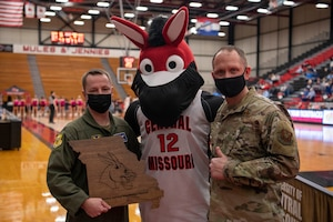 U.S. Air Force Col. Kyle Wilson, 509th Bomb Wing vice commander, left, and Chief Master Sgt. Jason Hodges, 509th BW command chief, right, pose for a photo with the University of Central Missouri mascot during the UCM Military Appreciation basketball game, Feb. 13, 2021, in Warrensburg, Missouri. Whiteman AFB and UCM share a valuable community partnership that fosters a supportive relationship between the base and local communities. (U.S. Air Force photo by Tech. Sgt. Dylan Nuckolls)