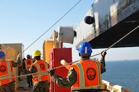 Sailors from Navy Cargo Handling Battalion 1 (NCHB 1) swing literage aboard the USNS 1st LT Jack Lummus (T-AK 3010) during an instream loading exercise.