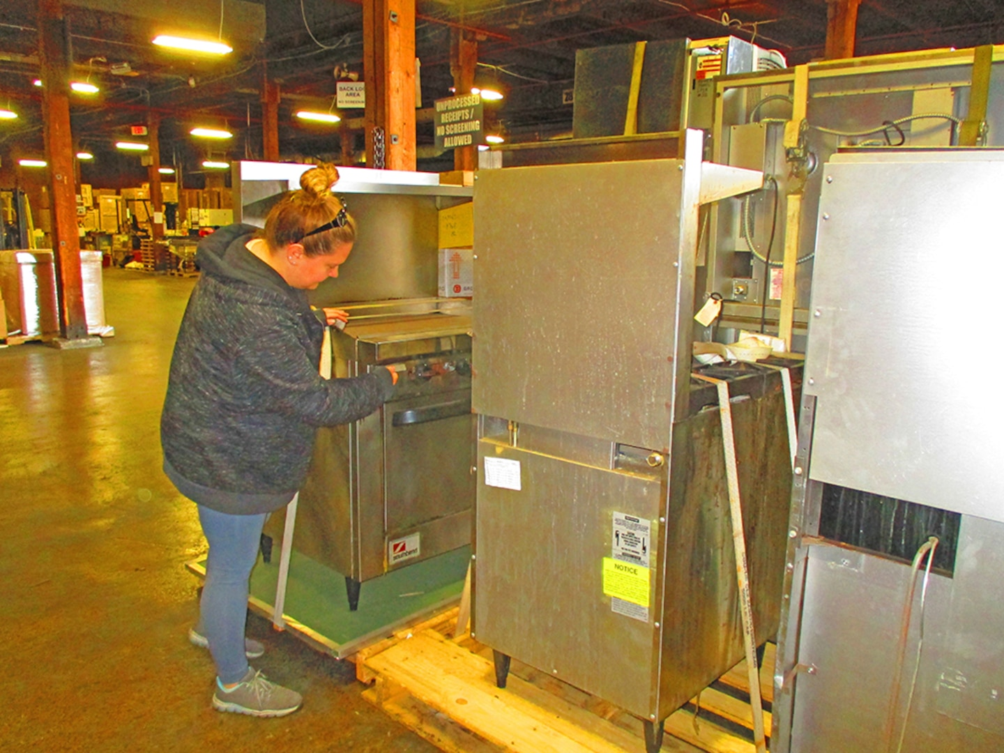 A warehouse worker prepares kitchen equipment for movement.
