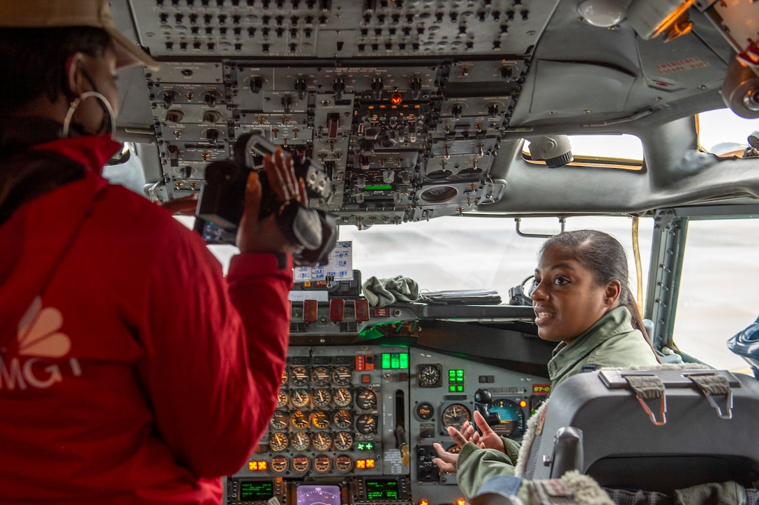 Photo shows woman sitting in cockpit of aircraft being interviewed on camera.