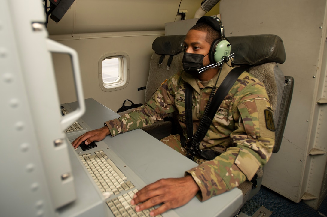Photo shows man sitting on aircraft in front of a monitor.
