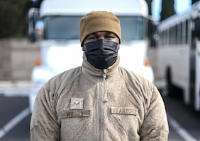 An Airman in a mask looks at the camera. It's mid-day