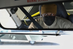 An Airman in a mask looks in a rearview mirror while driving a bus