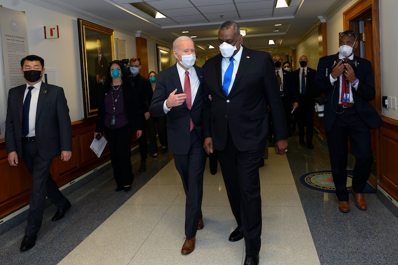 Two men dressed in business suits walk down a hall and talk followed by other people.