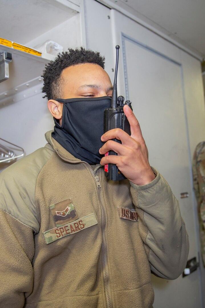 Photo shows Airman talking on hand radio.