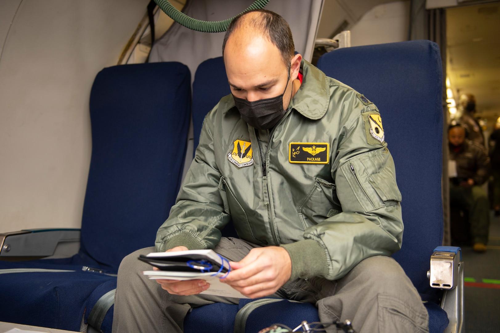 Photo shows man sitting in aircraft seat looking at manual.