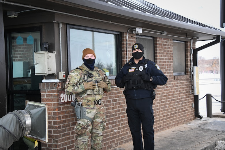 From left, Airman 1st Class Seth Chaffee, 97th Security Forces squadron force protection specialist, and Danny Thomas, 97th SFS flight sergeant, defend the main gate, Feb. 16, 2021, at Altus Air Force Base, Oklahoma. Working in 12-hour shifts during a weather emergency, security forces Airmen protected the base and kept Airmen and their families safe. (U.S. Air Force photo by Airman 1st Class Kayla Christenson)