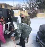 Airman 1st Class Aaron Bahn, 97th Wing Staff Agency (WSA) Commanders Administrative (CCA) mail clerk, assists a local family whose vehicle is stuck in the snow, Feb. 17, 2021, in Altus, Oklahoma. Airman Bahn and Airman Basic Jesse Robertson, 97th WSA CCA administrative technician, spent many hours assisting individuals who were stuck due to the winter weather storm that hit the City of Altus. (U.S. Air Force photo by Katey Graham)
