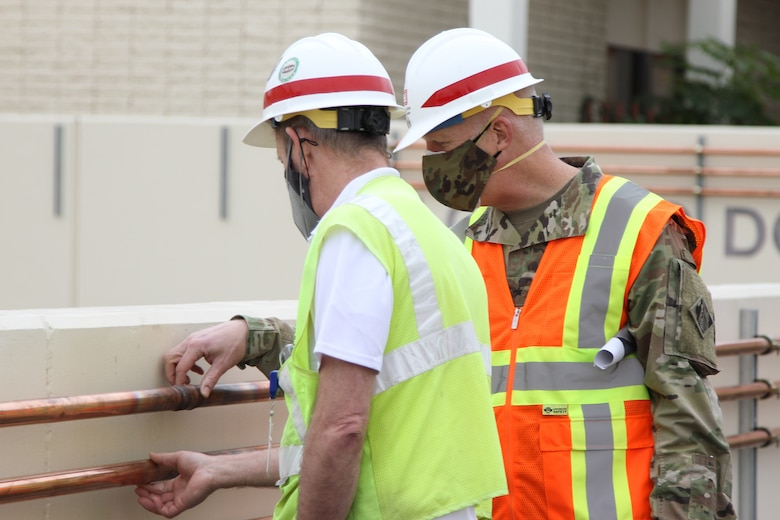 During his Feb. 9 visit to Beverly Community Hospital in Montebello, California, Brig. Gen. Paul Owen, U.S. Army Corps of Engineers South Pacific Division commander, right, joins Martin Reed, contracting officer's representative with the U.S. Army Corps of Engineers Rapid Response Technical Center of Expertise at the Omaha District, to examine newly installed copper tubing designed to safely transport specialized medical-grade gas mixtures for hospital patients.