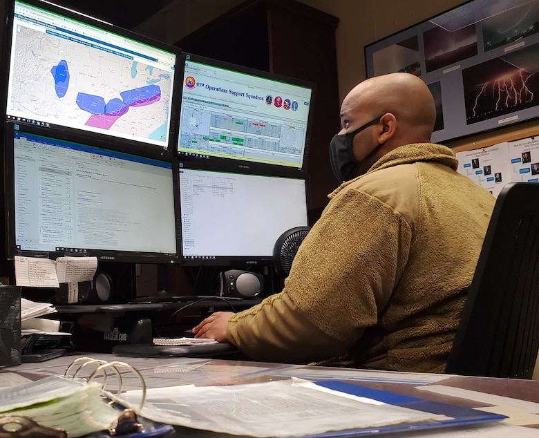 person looks at multiple computer monitors