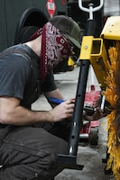 man replaces brushes on snow removal equipment