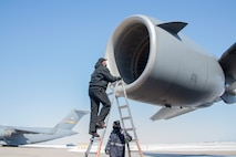 man on ladder looks at aircraft engine