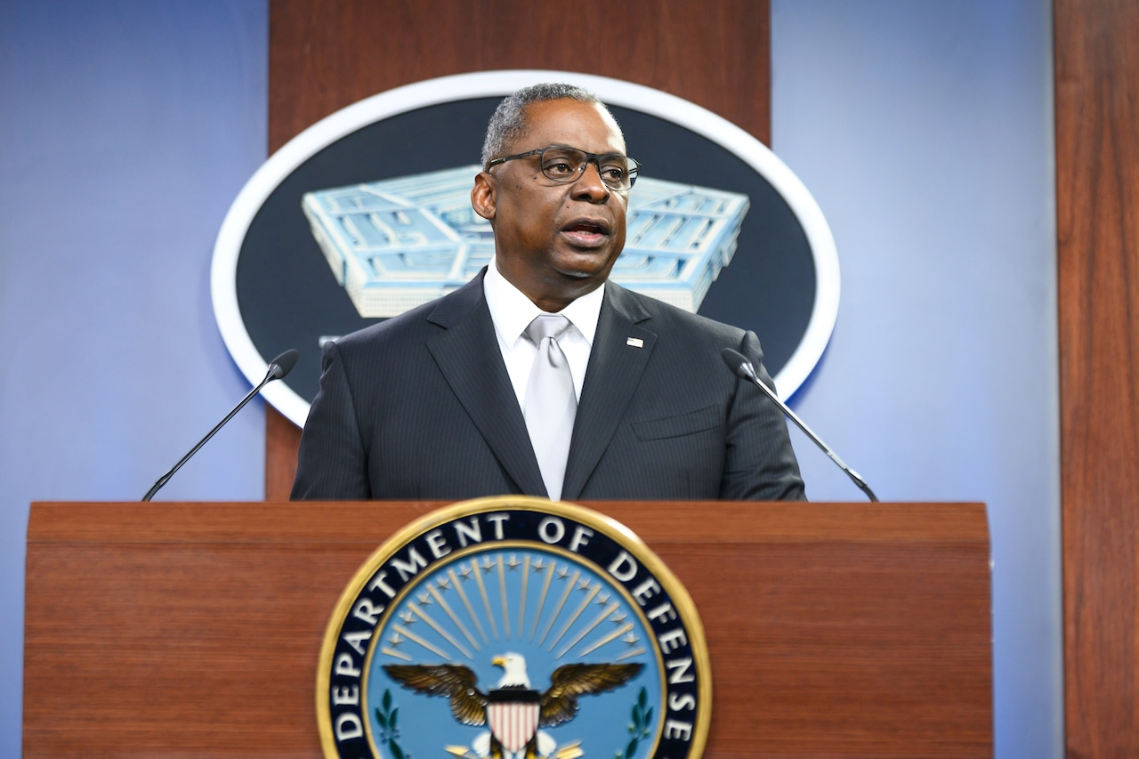 Secretary of Defense Lloyd J. Austin III stands and speaks at a lectern.