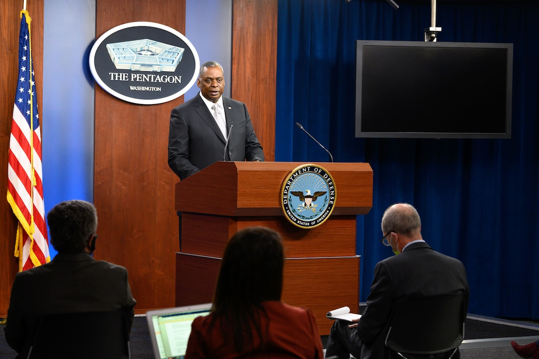 Secretary of Defense Lloyd J. Austin III stands and speaks at a lectern to seated audience members.