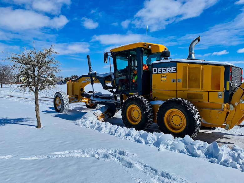 A member of the 17th Civil Engineering Squadron enhances the safety of the travel routes throughout the base by clearing snow on Goodfellow Air Force Base, Texas, Feb. 15, 2021. The 17th CES adapted and overcame the challenges of record-breaking snowfall with no proper removal equipment in order to continue the mission. (Courtesy photo)