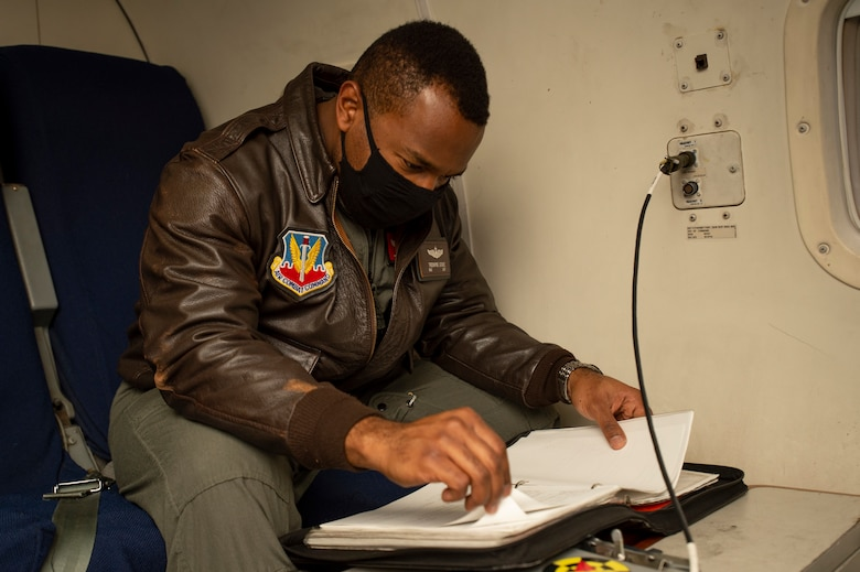 Photo shows man sitting in aircraft seat looking at a manual.