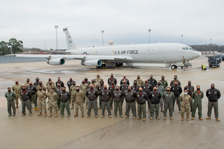 Photo shows group of Airmen standing in front of aircraft.