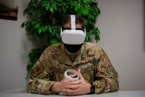 A man in uniform sits at a table weating a virtual reality headset while holding a virtual reality controller.