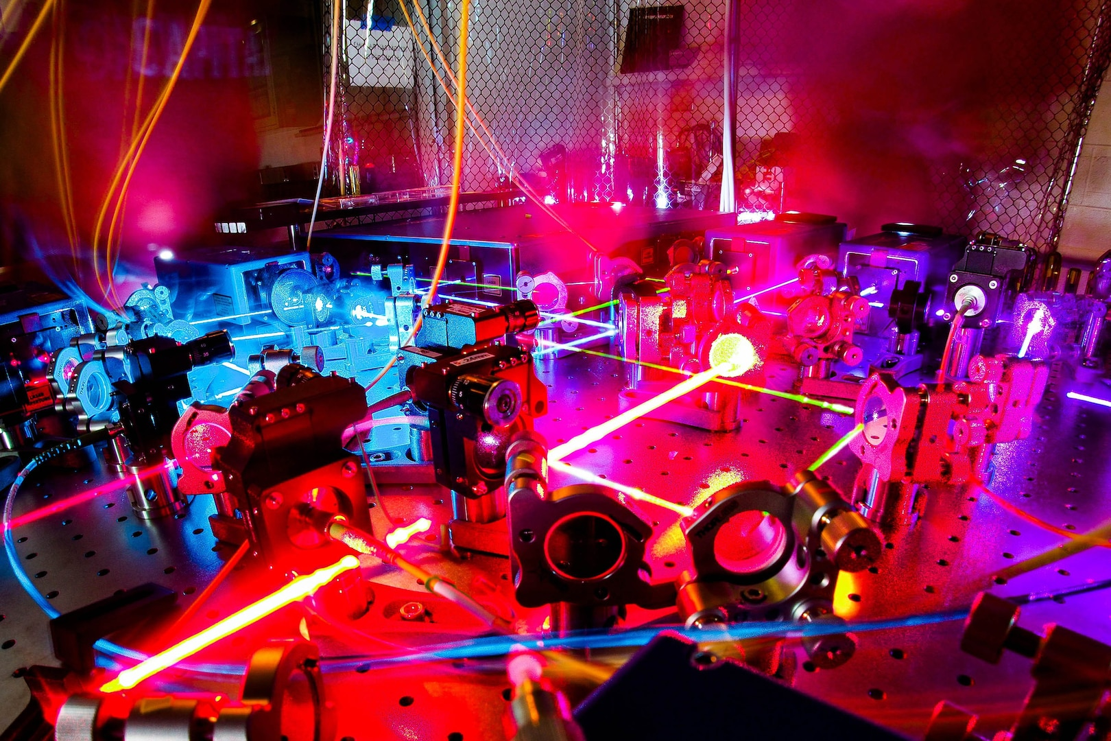 A large room filled with equipment is bathed in colorful lights.