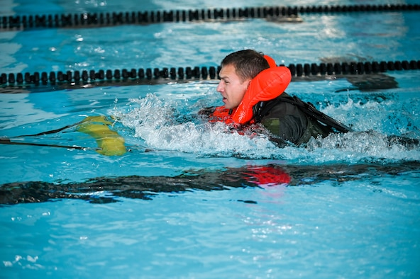 Lt. Col. Bart Wilbanks, an F-35A Lightning II pilot in the 419th Fighter Wing at Hill Air Force Base, Utah, simulates being dragged through the water while still attached to a parachute.