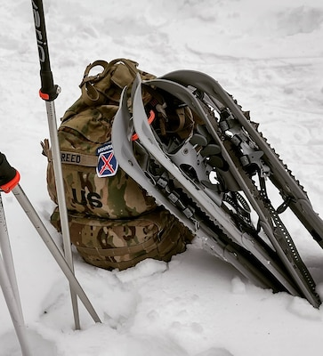 Army backpack with 10th Mountain Patch sits in the snow with snowshoes lying on top.