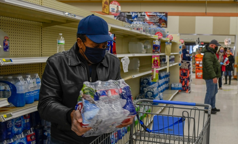 A commissary patron puts water in his cart at the Joint Base San Antonio-Randoph Commissary Feb. 19, 2021.