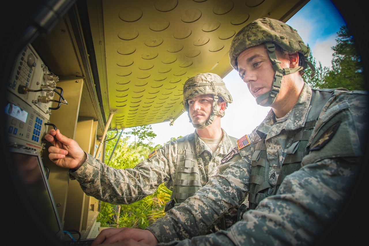 Two soldiers work with communications equipment.