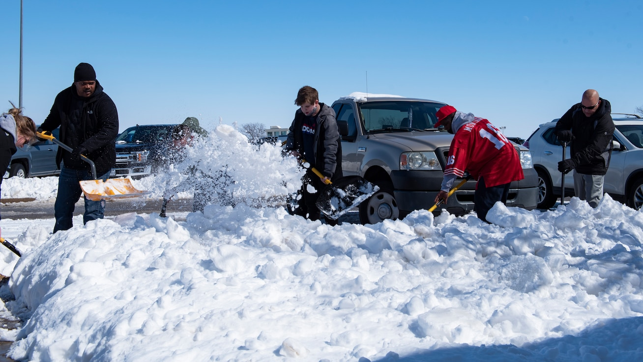 Volunteers clear off snow from a sidewalk  at Sheppard Air Force Base, Texas, Feb. 19, 2021. The installation received almost a foot of snow, more than two times its annual amount, crippling the technical and pilot training missions. (U.S. Air Force photo by Senior Airman Pedro Tenorio)