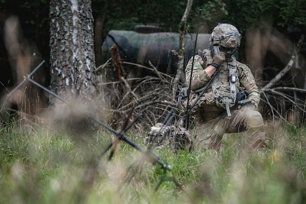A soldier in a wooded area talks on a radio.
