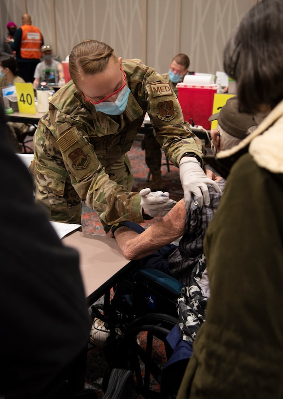 U.S. Air Force Tech. Sgt. Holley Bergfeld, a medic with the 142nd Medical Group, administers a COVID-19 vaccine at the Portland Convention Center, Portland, Ore., February 18, 2021. Members of the Oregon Air and Army National Guard are helping to facilitate COVID-19 vaccination distribution efforts throughout the state. (U.S. Air National Guard photo by Tech. Sgt. Steph Sawyer)